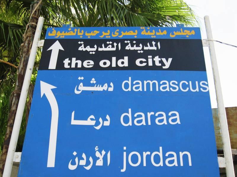 Papan penunjuk jalan dari Yordania ke Suriah. Sebelum perang terjadi, ibukota Suriah Damaskus sangat mudah dicapai lewat ibukota Yordania Amman.