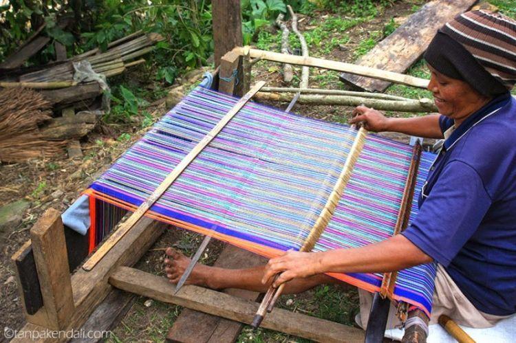 Seorang ibu sedang menenun kain songke