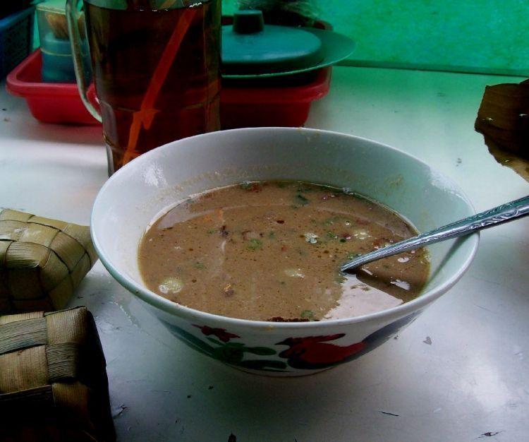 Seporsi Coto Makassar dengan kuah coklat yang gurih. Biar kenyang, bisa minta dipotongkan ketupat.