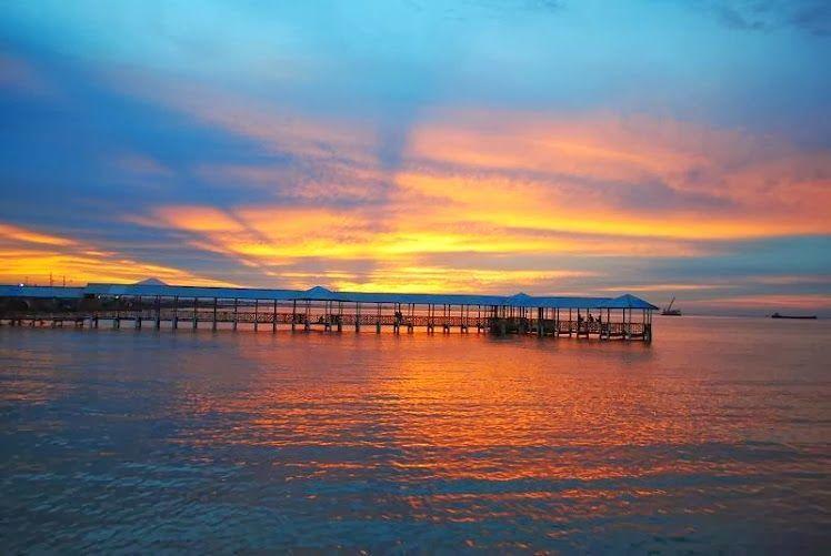 Matahari tenggelam di antara dermaga Pantai Alam Indah