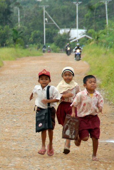 SAMBAS, 18/12. TRAFFICKING. Tiga anak berlari melewati jalan utama menuju Pintu Lintas Batas Indonesia-Malaysia di Kecamatan Sajingan, Kabupaten Sambas, Kalbar, Kamis (17/12). Adanya sejumlah permasalahan di daerah perbatasan selain keamanan adalah terjadinya praktek perdagangan manusia (trafficking) pada anak-anak. Hal tersebut dipicu oleh permasalahan keluarga di daerah perbatasan yaitu tidak menentunya penghasilan dan kemiskinan. FOTO ANTARA/Jessica Wuysang/pd/09