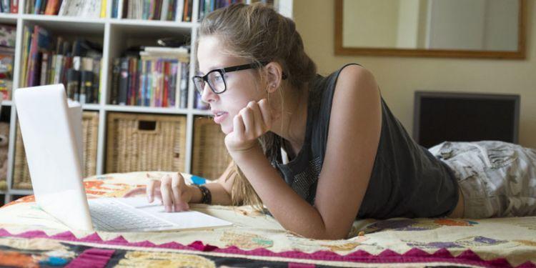 Teenage girl lying on front using laptop
