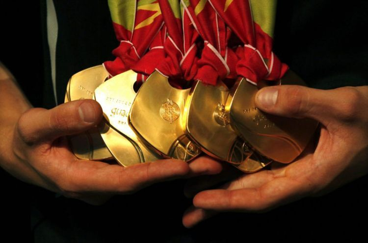 Brazil's swimmer Thiago Pereira holds his Pan-American medals during a media conference in Sao Paulo October 24, 2011. Pereira was crowned king of the Pan-American pool after won seven medals, five gold, one silver and one bronze. REUTERS/Paulo Whitaker (BRAZIL - Tags: SPORT SWIMMING)