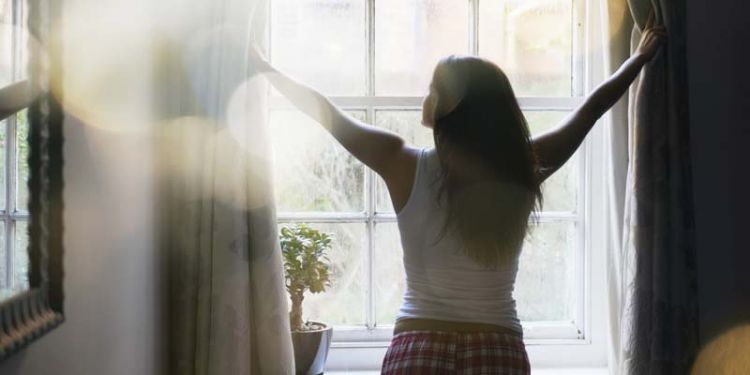 woman opening curtains in the morning