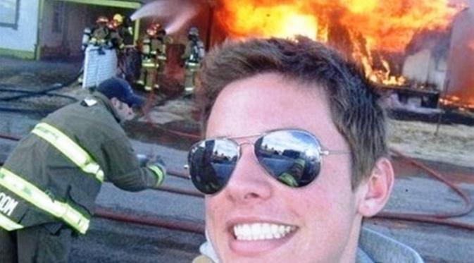 Seorang laki-laki berfoto dengan senyum lebar di lokasi kebakaran
