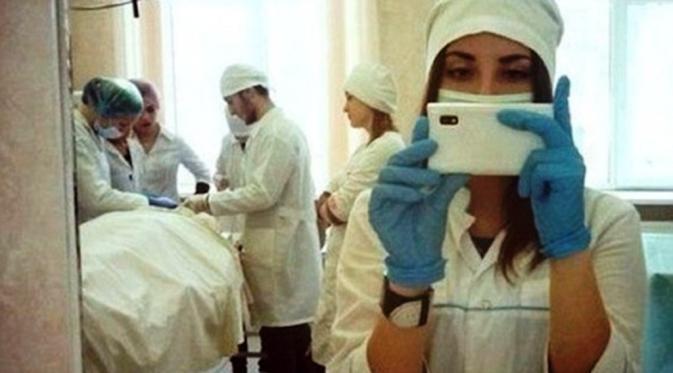 Seorang petugas medis berfoto dengan latar belakang pasien yang sedang dioperasi