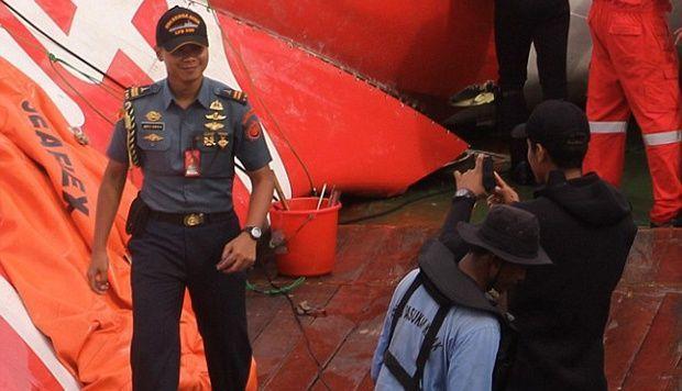 Oknum petugas yang berfoto di depan bangkai pesawat