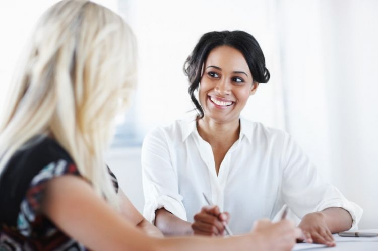 Two stress-free female co-workers look over the plans