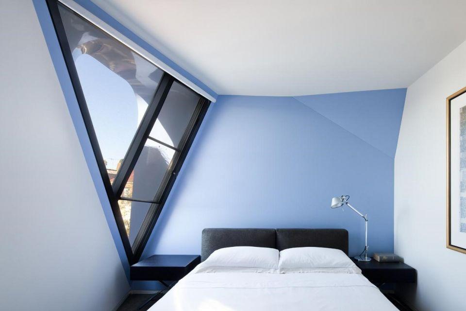 Kamar tidur dengan bentuk desain unik dan warna biru futuristik, karya Andrew Simpson