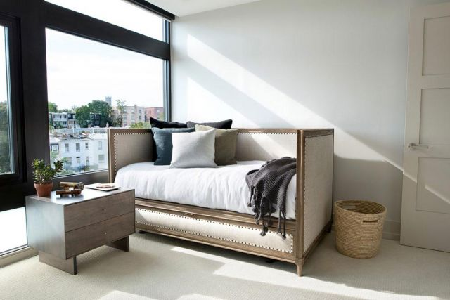 Sofa bed di sudut ruangan dekat jendela