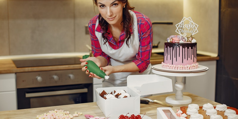 Women in icing a cake