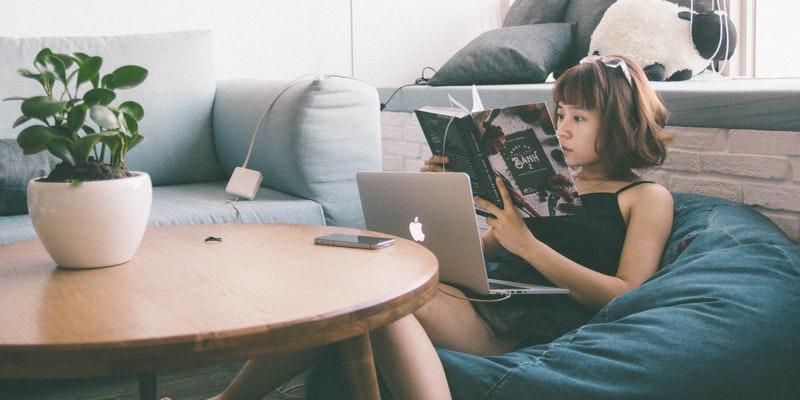 women sitting on bean bag using MacBook