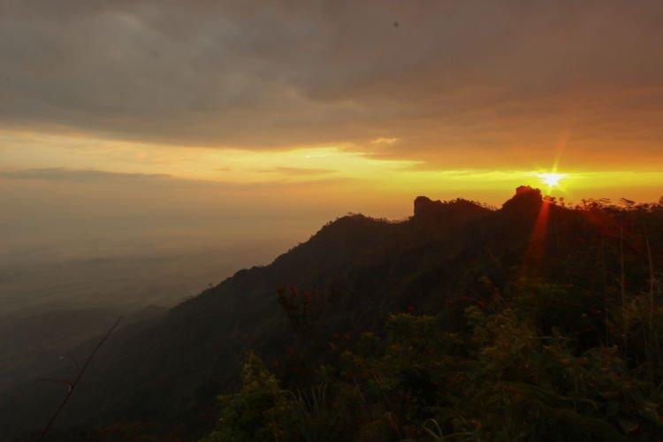 Sebermula cahaya dari timur di Puncak Suroloyo.