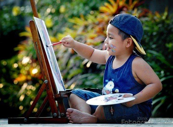 seorang anak tampak serius sedang belajar melukis dengan menggunakan media kanvas dan warna.