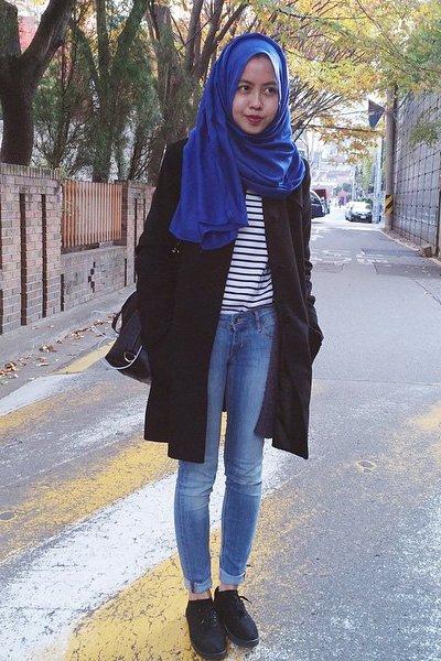 Tampil ala Eropa dengan jeans dan coat hitam ini.
