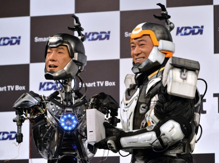 Japanese actor Ken Matsudaira (R), clad in a robot suit, smiles with an android robot (L) in his likeness called