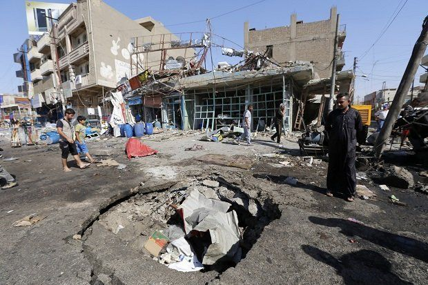 A man looks at the crater caused by an explosion after a car bomb attack in Baghdad's al-Ghadeer district, September 12, 2014. REUTERS/Thaier Al-Sudani (IRAQ - Tags: CIVIL UNREST POLITICS)