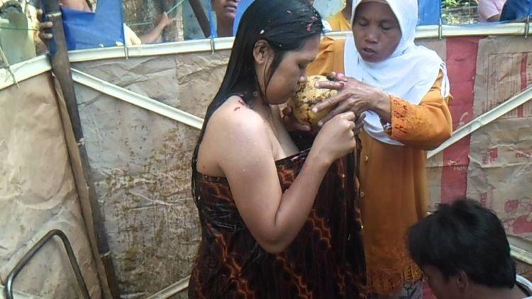 si nenek memasukkan kelapa gading ke jarik ibu