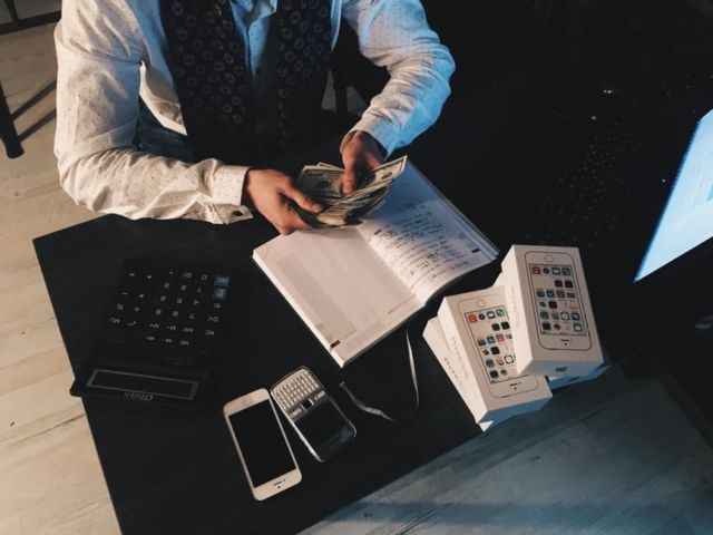person-counting-money-with-smartphones-in-front-on-desk