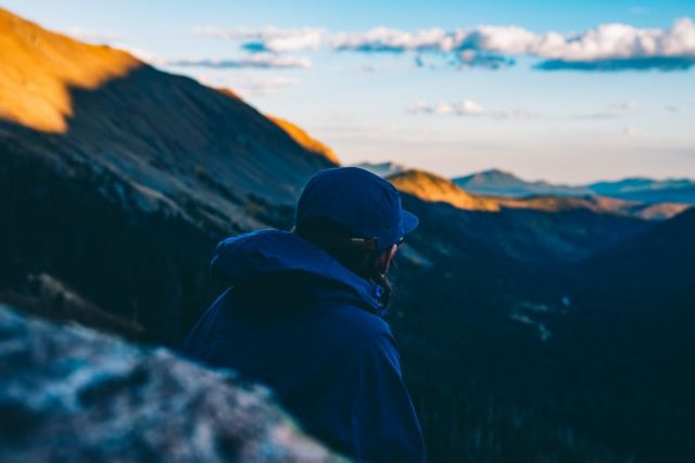 man-in-blue-hoodie-standing-on-mountain-cliff-during-daytime