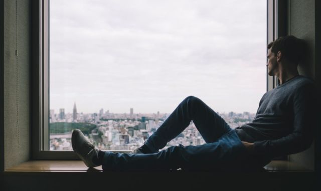 man-sitting-near-window-viewing-outside-buildings-during-daytime