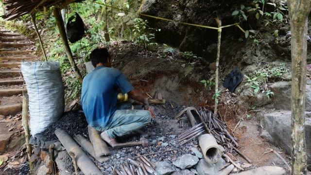 bapak ini sedang memahat batu tebing untuk pemakaman