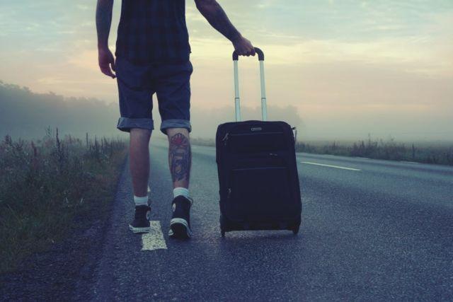 man-walking-on-the-road-holding-black-luggage