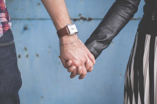 2-person-holding-hands-besides-blue-painted-wall