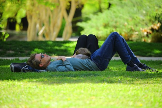 man-wearing-blue-long-sleeve-shirt-lying-on-ground-during-daytime