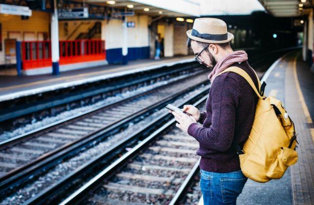 brown-hoodie-standing-in-front-of-train-railway