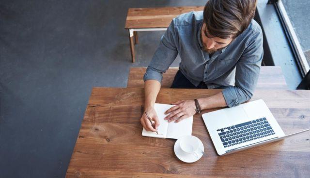 man writing blog post in coffee shop