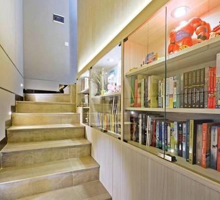 Rak buku di dinding area tangga di Citra Garden House oleh Studio Denny Setiawan