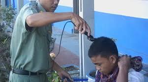 Murid mendapatkan pangkas rambut gratis