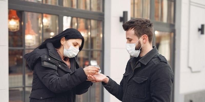 Women-Putting-Hand-Sanitizer-on-Man-s-Hand