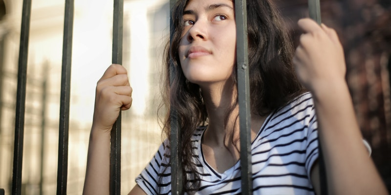 Sad isolated young women looking away through fence