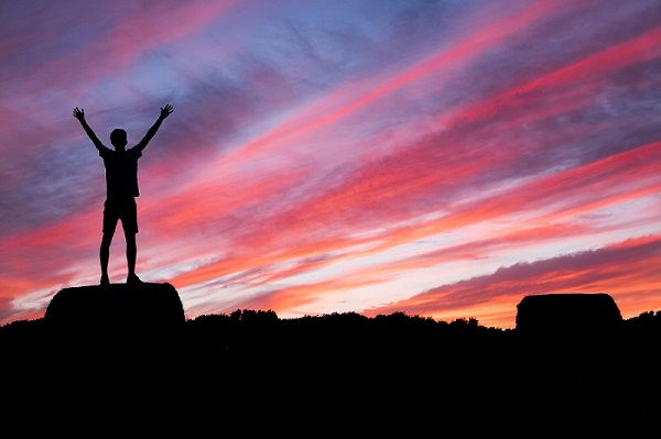 silhoute of man standing on high ground under red and blue skies