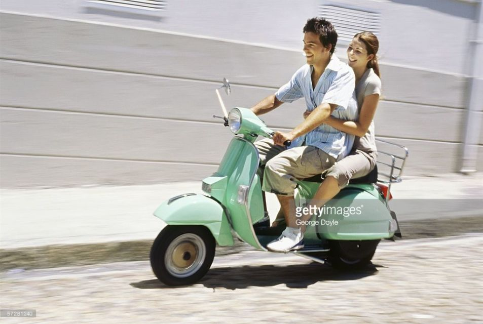 Young couple riding on a scooter and smiling (George Doyle/getty image)