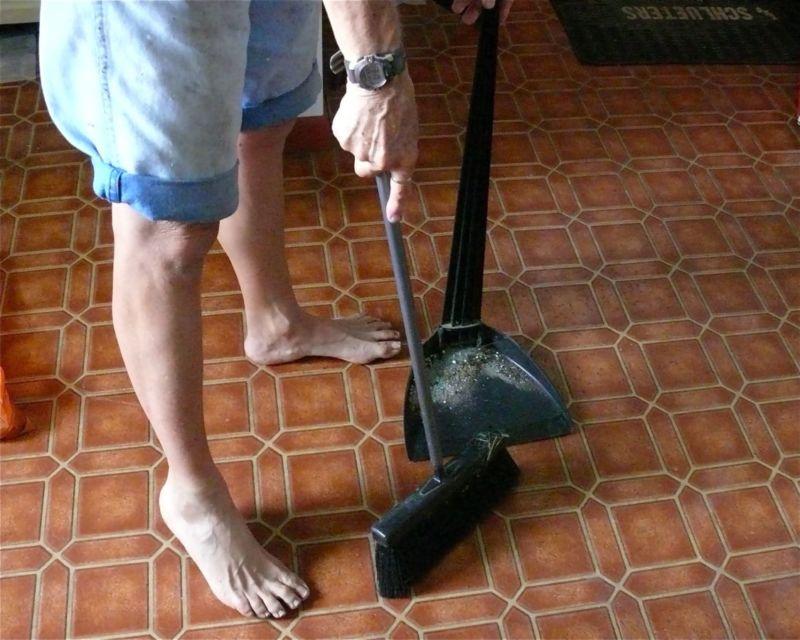 menyapu lantai menggunakan sapu